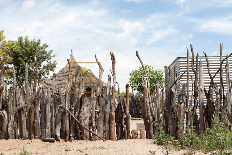 The Ovambo people in the rural North of Namibia still live in traditional homesteads, with some modern elements like brick or metal sheet huts and plastic chairs. The homestead is protected by an outer wall made of mopane poles.