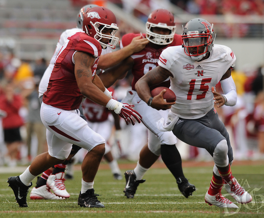 NWA Media/ANDY SHUPE - Arkansas defensive end Tevin Beanum, left, pursues Nicholls quarterback Kalen Henderson during the second quarter Saturday, Sept. 6, 2014, at Razorback Stadium in Fayetteville