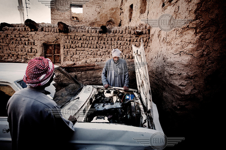 A man looks at the engine of his 30 year old Mazda in El Qasr.