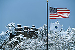 The American flag waving in the winter wind in front of the ruins of an old stone house, Estes Park, Colorado, USA