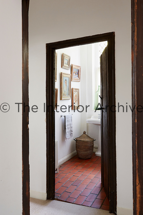View into a bathroom, with red tiled floor and picture frames