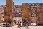 The ruins of the Triumphal Arch or Hadrian Gate, built by the Romans on the Colonnade Street in the ruins of the Nabataean city of Petra in the Hashemite Kingdom of Jordan.  Petra Archeological Park is a Jordanian National Park and a UNESCO World Heritage Site.  The Corinthian Tomb in the Royal Tombs is visible in the background.