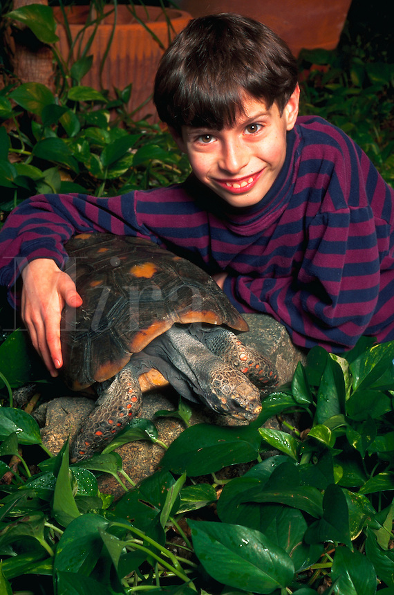 Portrait of a smiling boy with his unusual pet - a Red Foot Tortoise.