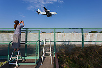 Kumiko, a female military aircraft enthusiast films a Kawasaki P1 Maritime Reconnaissance aircraft with the Japanese Self Defence Forces landing at Naval Air Facility, Atsugi,near Yamato, Kanagawa. Japan. Thursday April 25th 2019