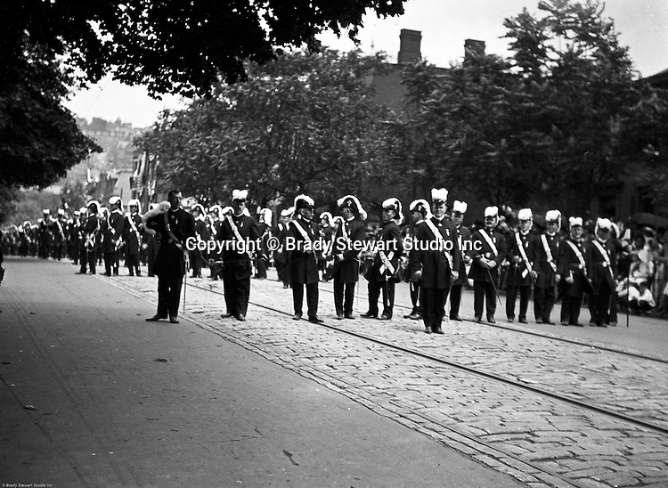 Pittsburgh PA:  Pittsburgh-area Manson marching in the annual St Patrick's Day Parade - 1903.  View of Homer Stewart and fellow Masons preparing to march with crowds on both sides of the street.