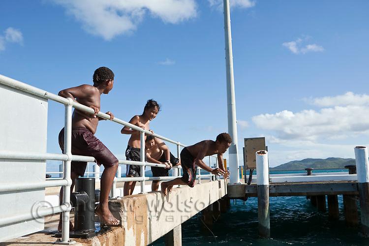 Islander kids leap off a boat at the jetty.  Thursday Island, Torres Strait Islands, Queensland, Australia