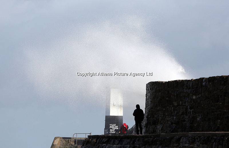 WINDY WEATHER WALES<br /> Pictured: A man tries to take cover as a wave hits the wall by the lighthouse in Porthcawl, south Wales, UK. Tuesday 06 June 2017<br /> Re: Strong winds have been affecting parts of the UK