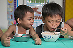Eight-year old Lance Macapanas (right) eats soup as his 6-year old friend Luigi looks on in the United Methodist Church in the Parola neighborhood of Tondo, a poor section of Maniila, Philippines. Nursing students from the Mary Johnston College of Nursing regularly visit the neighborhood to do health education and monitor the health of residents, at the same time running  a feeding program for neighborhood children.<br /> <br /> The nursing school is supported by United Methodist Women.