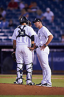 Tampa Yankees pitching coach Tim Norton (right) talks with catcher Santiago Nessy (19) and pitcher Ian Clarkin (24) during a game against the Lakeland Flying Tigers on April 8, 2016 at George M. Steinbrenner Field in Tampa, Florida.  Tampa defeated Lakeland 7-1.  (Mike Janes/Four Seam Images)