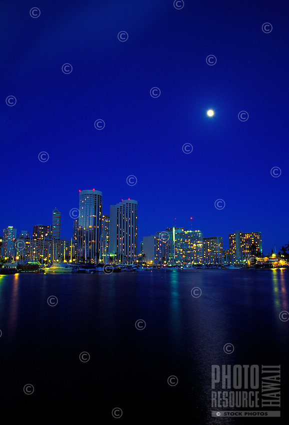 Honolulu at night with the moon and alawai harbor.