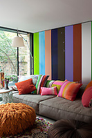In the living room, a NeoWall sofa designed by Piero Lissoni has been dressed with brightly coloured, striped cushions. Distinctive Rasta floor cushions create additional seating or a foot rest