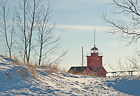 "A snow covered foredune blocks the view of the botton of Holland's ""Big Red"" Lighthouse, Holland, Ottawa, Michigan"