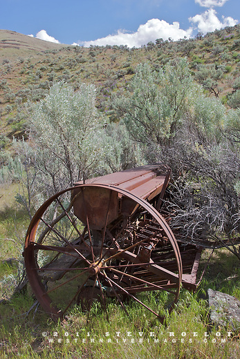A rusting ranch implement surrounded by sage in the John Day River valley, Oregon.