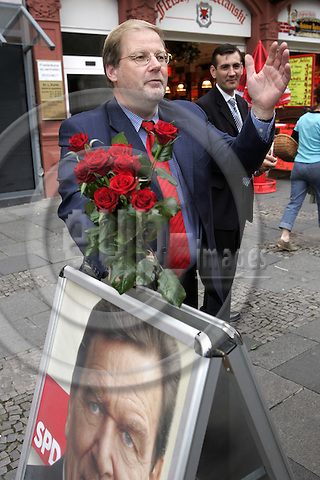 SCH?NINGEN - GERMANY-- 15 - SEPTEMBER - 2005 -- Hans-J?rgen UHL candidate and MP for SPD during his election campaign giving roses to potential female voters. The poster of Gerhard Schr?der in front of him. -- PHOTO:  JUHA ROININEN / EUP-IMAGES