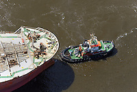 Hamburger Hafenschlepper zieht ein Schiff: EUROPA, DEUTSCHLAND, HAMBURG, (EUROPE, GERMANY), 20.02.2012  Schlepper, auch Schleppschiffe genannt, (engl. tugboat oder tug) sind Schiffe mit leistungsstarker Antriebsanlage, die zum Ziehen und Schieben anderer Schiffe oder großer schwimmfaehiger Objekte eingesetzt werden. Meist werden zum Ziehen Schlepptrossen verwendet, die am Schlepper an Haken eingehaengt oder an Seilwinden aufgerollt sind. In Deutschland gibt es zusammen mit den Schubschiffen 450 Stueck