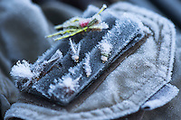 Ice crystals cover flies on a fishing vest while fishing in western Montana.