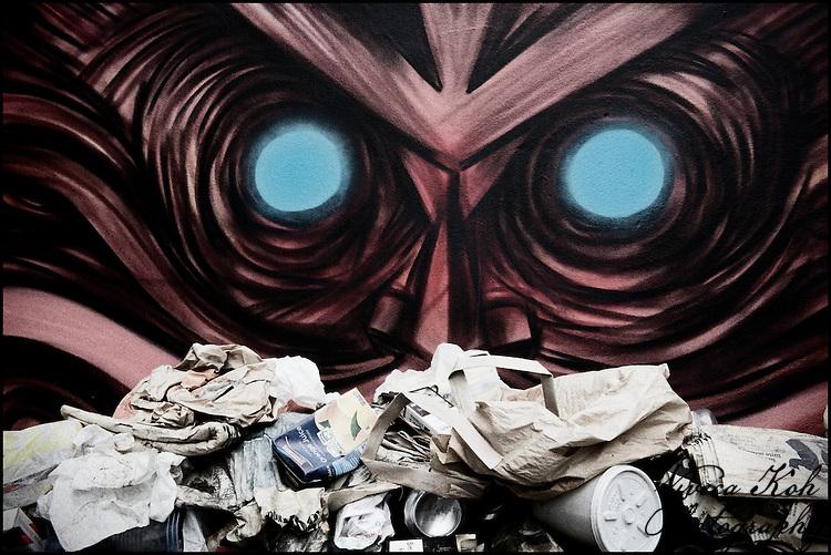 Street art by DanK overlooking rubbish, Shoreditch, East London