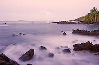 The moon sets with misty water and rocks in the foreground at Makena, Maui.