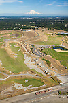 remnants from the site's past as a sand and gravel mine lie adjacent to the 18th hole in this aerial view of Chambers Bay Golf Course looking roughly southeast with Mount Rainier behind, site of the 2015 US Open Championship; University Place, WA near Tacoma