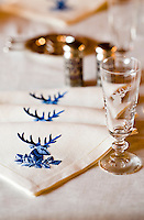 A set of white linen napkins has been embroidered with the head of a stag in blue