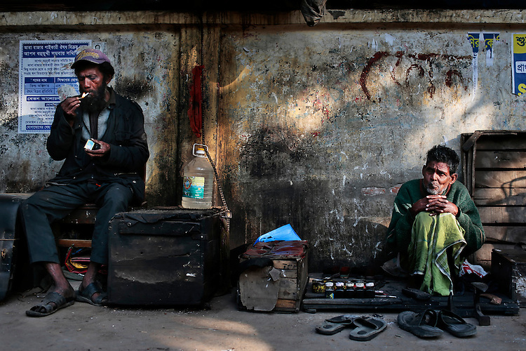 A Bangladeshi cobbler awaits customers by a way side, as a man lights a cigarette in Dhaka, Bangladesh.