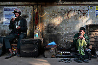 A Bangladeshi cobbler awaits customers by a way side, as a man lights a cigarette in Dhaka, Bangladesh.