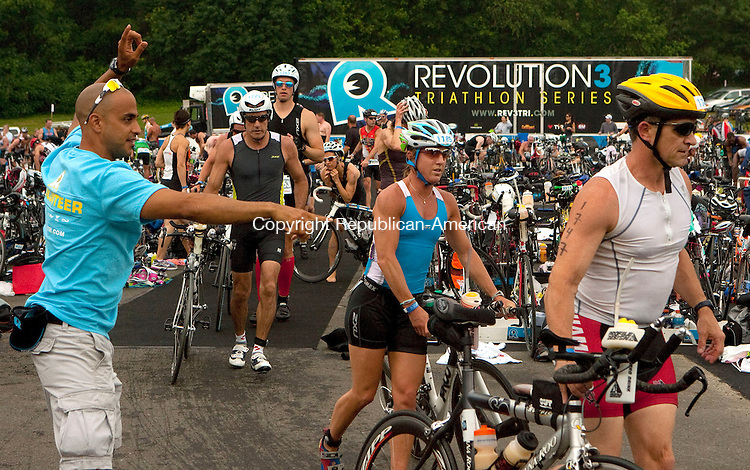 MIDDLEBURY, CT 06 JUNE, 2010-060610JS1-Volunteer Leo Katsetos, an athletic trainer at Fairfield University and Triathlete, left, directs racers out of the staging area during the Revolution3 Half-Ironman Triathlon Sunday at Quassy Amusement Park in Middlebury. Katsetos is one of more than 500 volunteers who make sure the event runs smoothly. <br /> Jim Shannon Republican-American
