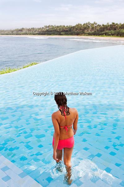 A young woman enters the main ocean-view infinity pool at Saman Villas, Aturuwella, Bentota, Sri Lanka.