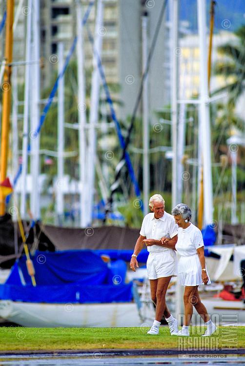 Attractive senior couple wearing white tennis clothes walk by boats at the Ala Wai Yacht Harbor near Waikiki.
