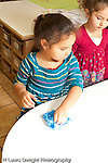 Education preschool 3-4 year olds clean up time girl wiping table with sponge rag vertical