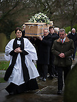© Joel Goodman - 07973 332324 . 6 December 2013 . Marple , UK . Bob's coffin is carried to St Thomas's Parish Church in Mellor , lead by the Vicar Rev. Alex Sanders . The funeral of farmer Bob Watson . His son David Watson drives his father's coffin on a trailer hooked to the back of Bob's favourite tractor through Marple via Bob's local pub before taking it on to the church . Photo credit : Joel Goodman