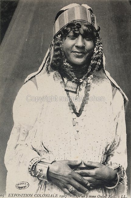 Ouled Nail tribal woman from Saharan Africa wearing traditional jewellery and headdress, at the Colonial Exhibition of 1907, held in the Jardin d'Agronomie Tropicale, or Garden of Tropical Agronomy, in the Bois de Vincennes in the 12th arrondissement of Paris, postcard from the nearby Musee de Nogent sur Marne, France. The garden was first established in 1899 to conduct agronomical experiments on plants of French colonies. In 1907 it was the site of the Colonial Exhibition and many pavilions were built or relocated here. The garden has since become neglected and many structures overgrown, damaged or destroyed, with most of the tropical vegetation disappeared. The site is listed as a historic monument. Picture by Manuel Cohen / Musee de Nogent sur Marne