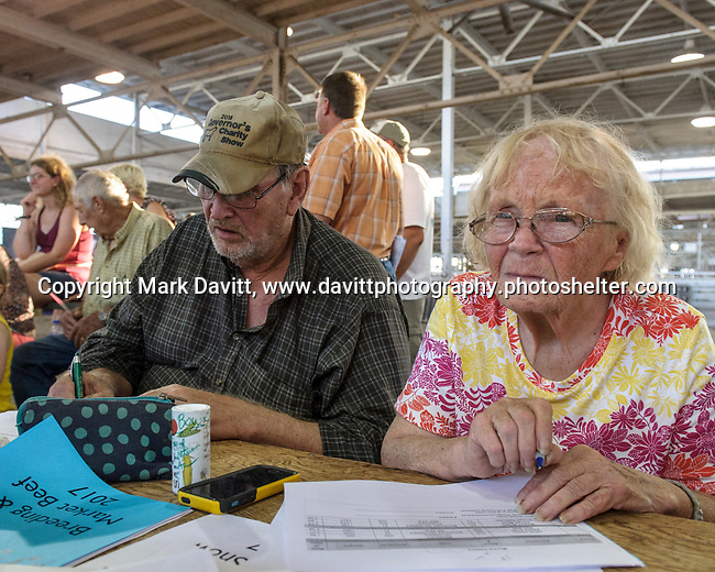 John Bowie and his wife Verna of Runnells volunteer to help keep records for the Polk County Fair cattle show July 21.