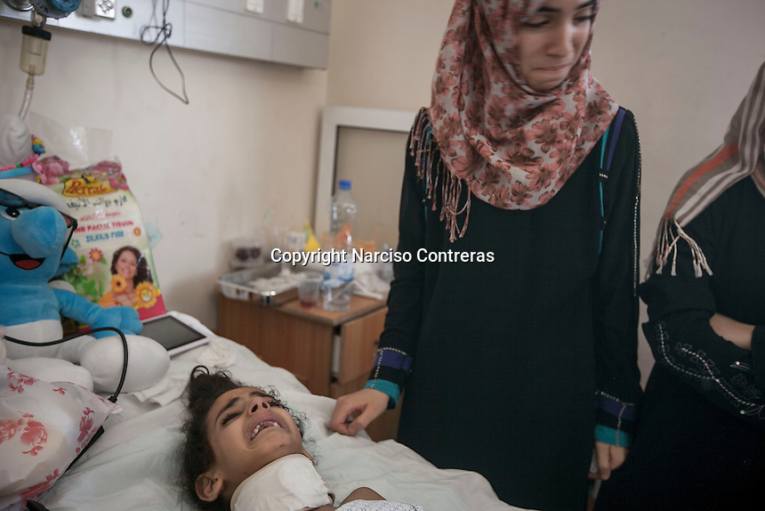 """In this Saturday, Aug. 16, 2014 photo, Maha Shaik Khalil, a 7 yo girl, cries as she lies helplessness on a bed in Al-Shifa hospital in Gaza City. Maha survived after an Israeli bomb targeted her family house in Shuyaja neighborhood during the """"Protective Edge"""" military operation in Gaza Strip. Maha is totally paralized from neck down her body due the severe wounds at her spinal nerves. (Photo/Narciso Contreras)"""