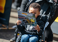 Feb 9, 2019; Pomona, CA, USA; A young NHRA fan looks at a handout driver autograph card from funny car driver J.R. Todd during qualifying for the Winternationals at Auto Club Raceway at Pomona. Mandatory Credit: Mark J. Rebilas-USA TODAY Sports