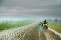 Motorcycle riders drive through a rain storm on the muddy, unpaved section of dirt road on the James Dalton highway, Interior, Alaska.
