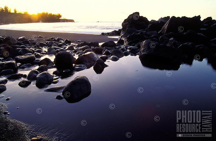 Large lava rocks frame a pond during sunset at the black sand Kehena Beach on the Big Island of Hawaii.