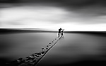 Conceptual beach scene with male pushing cycle across sandy beach towards sunlight