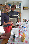 Model released boy and girl twins making a cake together in family kitchen, UK