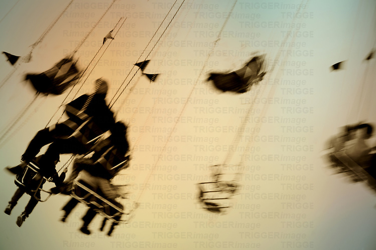The abstract silhouettes of sitting visitors on a rotating swing ride.