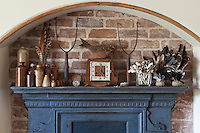 An interesting collection of objects is displayed on the mantelpiece of the living room fireplace with an antique fish-shaped clock as a focal point in the centre