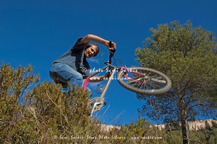 Man making jumps through bushes on his mountain bike, Vitrolles, Provence, France.