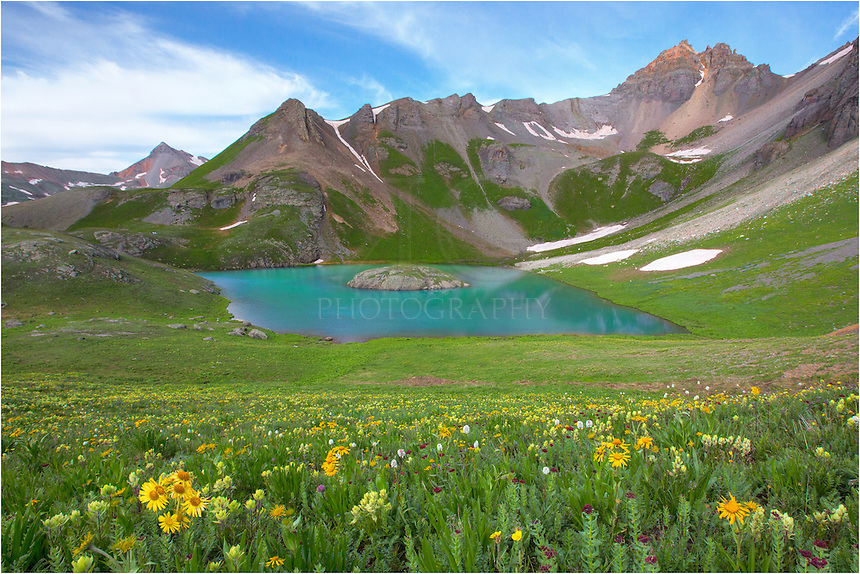 At 12,500 feet and nestled in a cirque beneath US Grant Peak, Island Lake is a sight for a tired hiker. The trek starts at the Ice Lakes Trailhead, about 5 miles from Silverton down South Mineral Road. The landscapes and vistas that await you are worth the effort, as the aquamarine lake shows colors rarely seen at lower altitudes. Along the path, you'll enjoy a myriad of Colorado wildflowers, perfect for the avid photographer and wildflower enthusiast. <br /> <br /> Meadows of Columbine and daisies fill rest near Lower Ice Lake, and the columbine stretch up the slopes until you are nearly at Island Lake. Also, paintbrush, aster, Old Man of the Mountain, and other colorful varieties of wildflowers will line your trail.<br /> <br /> Get up early, though. This trail, at least to Lower Ice Lake, is popular. I was on the trail for this Colorado location by 4:45am and had this landscape all to myself. However, on the trail back to the car, I bet I passed 25 people heading up.