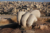 Fragment of colossal Roman Statue, Amman Citadel, Jabal al-Qal'a, Amman, Jordan. This hand fragment belonged to a colossal statue from the Roman period and was found near the Temple of Hercules. The statue is estimated to have stood over 13 metres high making it one of the largest statues from Greco-Roman times. Due to the massiveness of the statue, the temple was attributed to Hercules who was renowned for his physical strength. Downtown Amman cityscape visible in the background. Picture by Manuel Cohen