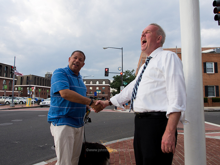 Councilmember and mayoral candidate Tommy Wells greets Eugene Kinlow in the Anacostia neighborhood of Washington, DC.