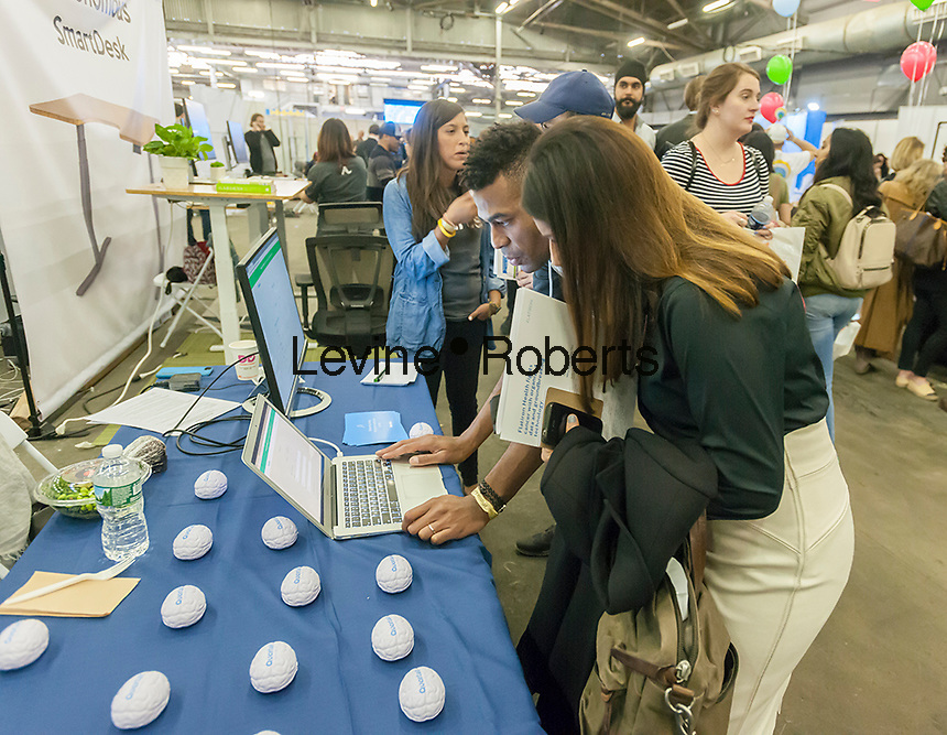 Workers from Quartet speak to attendees at the TechDay New York event on Tuesday, April 18, 2017. Thousands attended to seek jobs with the startups and to network with their peers. TechDay bills itself as the U.S.'s largest startup event with over 500 exhibitors. (© Richard B. Levine)