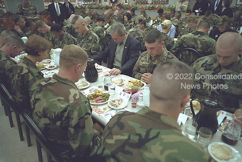 United States President George W. Bush prays with troops before sharing Thanksgiving dinner at Fort Campbell, Kentucky, Wednesday, November 21, 2001..Mandatory Credit: Eric Draper - White House via CNP.