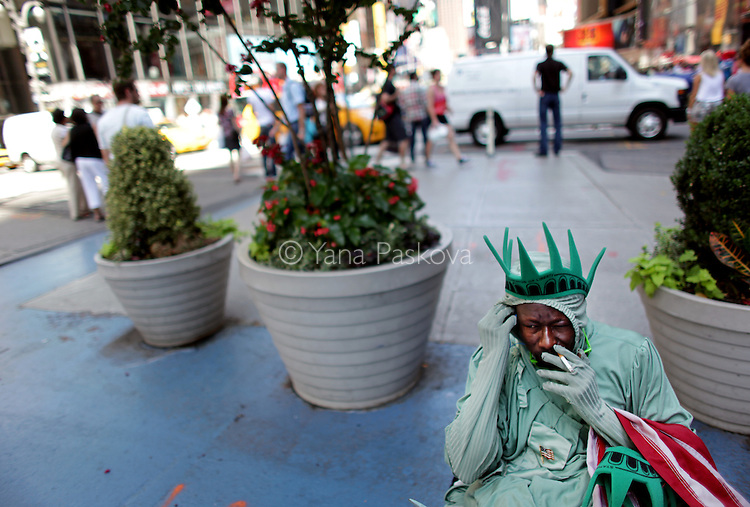 Amadou Tandia takes a smoking break from posing for tourist photos dressed as the Statue of Liberty in Times Square in Manhattan, New York on Monday, August 13, 2012. (Photograph by Yana Paskova for The New York Times)