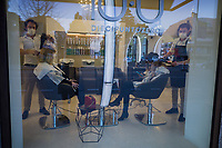 Switzerland. Canton Ticino. Lugano. «Diecipuntozero» is a hairdressing salon. Two men, both stylists, wear a mask on their faces to protect themselves from the Coronavirus (also called Covid-19). They stand up and style hair to two women seated on chairs. 13.03.2020 © 2020 Didier Ruef