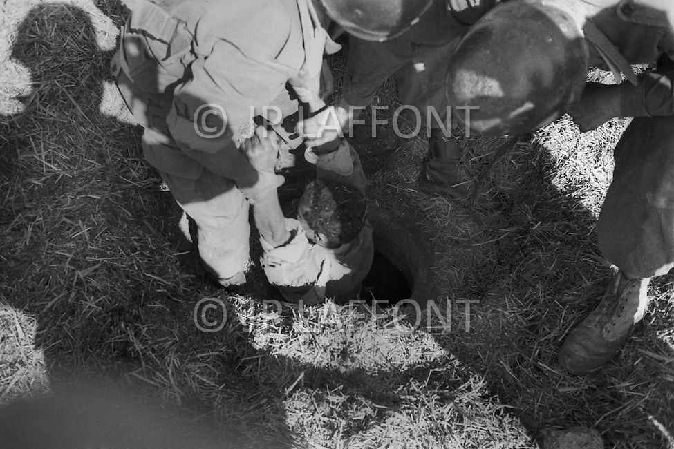Mascara Area, Algeria, Summer 1961. Harkis from M'Zaourat post, during a routine operation. They are part of the 158th Infantery Batallion based in Mascara. A suspect is removed from a man hole.
